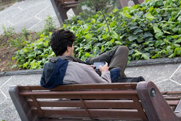 فردی در حال بازی با موبایل در پارک